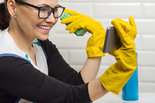 Hausfraufrau säubert im badezimmer und spricht am telefon.