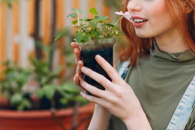 Hausgarten-konzept. junge hübsche frau mit blumentopf, der blumen riecht und lächelt. pflanzen pflanzen. frühlingshausgartenpflanze.