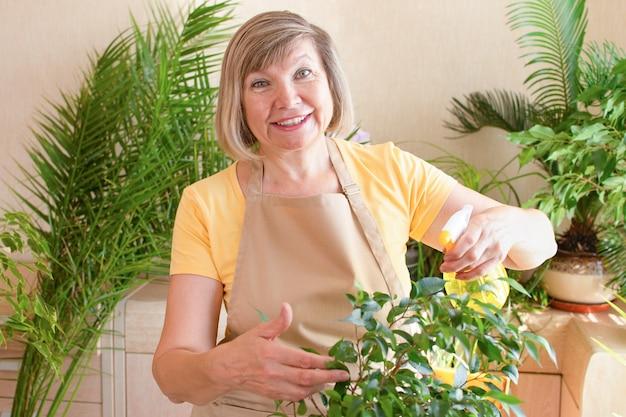Hausgartenarbeit ältere frau, die pflanzen mit einer sprühflasche besprüht ältere frau
