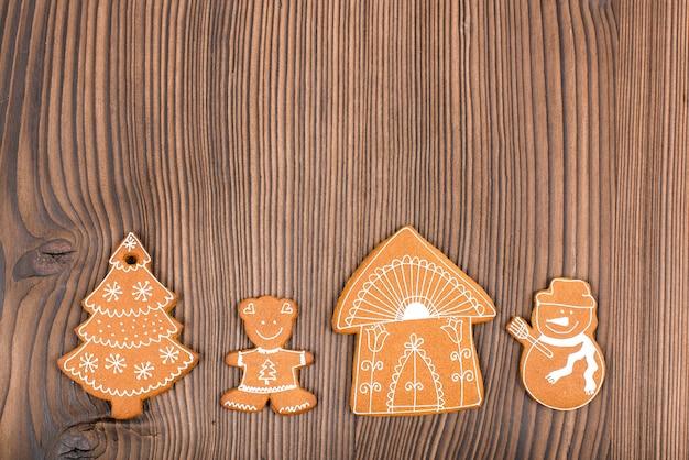 Hausgebackener und verzierter lebkuchen auf hölzernem hintergrund. weihnachts-lebkuchen