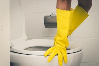 Hausgehilfin, die gelben Gummihandschuh trägt und Bürstenreinigung in der Toilette verwendet