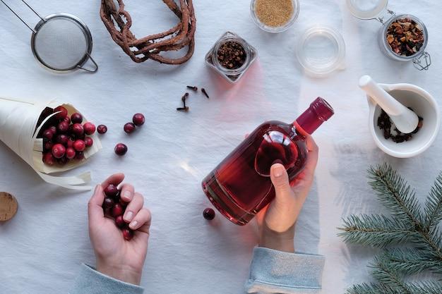 Hausgemachte alkoholische getränkezubereitung. flach auf cranberry-tinktur mit ethanol, beeren und gewürzen liegen.