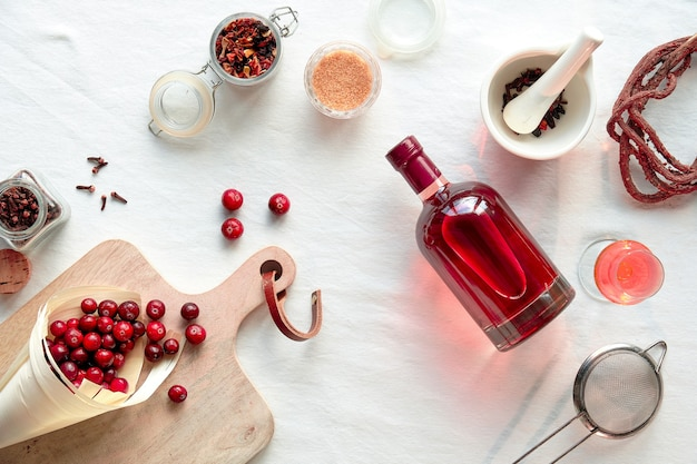 Hausgemachte alkoholische getränkezubereitung. flache lage, draufsicht auf selbstgemachte cranberry-tinktur.