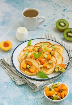 Hausgemachte amerikanische pfannkuchen mit obstsalat aus aprikose und kiwi