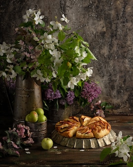 Hausgemachte apfel-zimt-scones mit lila blüten und apfelblühenden zweigen