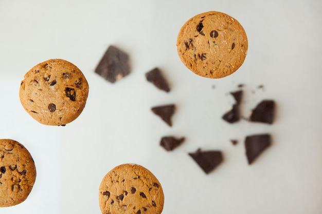 Hausgemachte back- und dessert-schokoladenkekse fliegen schokoladenkekse mit krümel auf grau