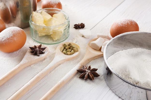 Hausgemachte bäckerei, zutaten zum backen auf weißem rustikalem holzküchentisch - butter, eier, mehl und gewürze, nahaufnahme