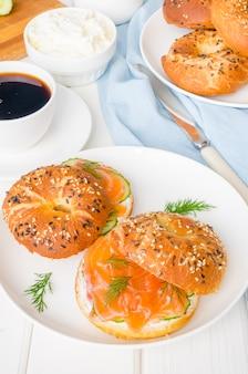 Hausgemachte bagels mit frischkäse, gurke und räucherlachs zum frühstück