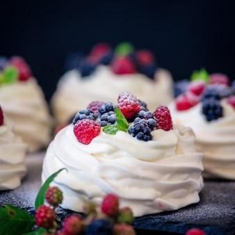 Hausgemachte baiser-basis für kuchen pavlova mit frischen blaubeeren und blackberry und puderzucker auf schwarzer betonstrukturoberfläche