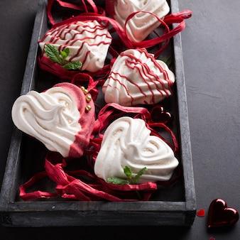 Hausgemachte baiser in herzform in alter holzkiste zum valentinstag