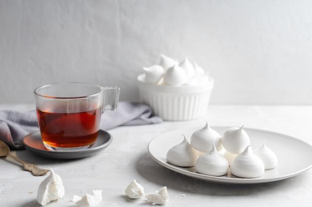 Hausgemachte baiser und tasse tee auf grauem hintergrund