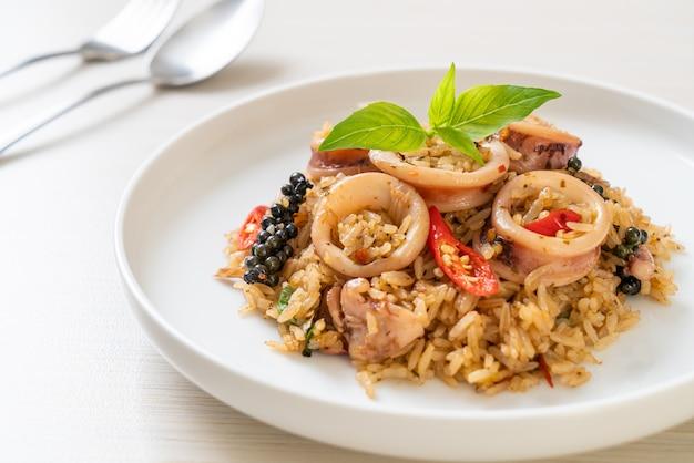 Hausgemachte basilikum und würzige kräuter gebratener reis mit tintenfisch oder tintenfisch - asiatische art zu essen
