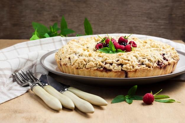 Hausgemachte beeren-shortcrust-torte mit streusel auf einem teller auf holztisch. speicherplatz kopieren