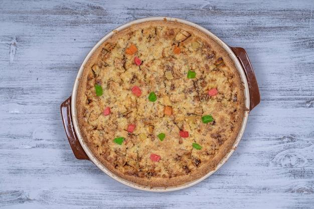 Hausgemachte bio-apfelkuchen-dessert verzehrfertig, nahaufnahme. apfelkuchen mit walnuss und kandierten früchten. nahaufnahme, ansicht von oben