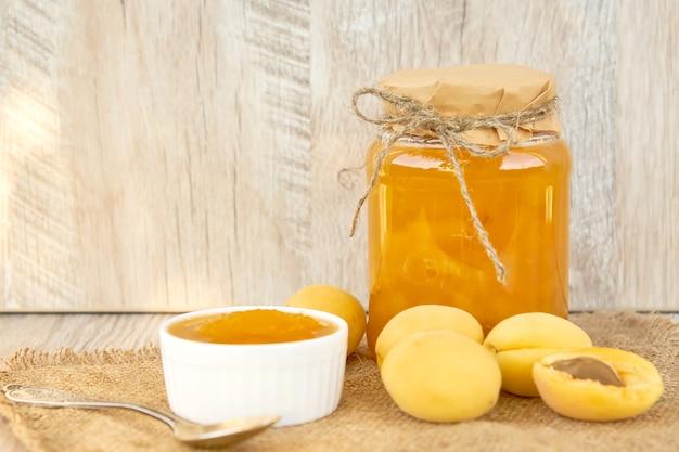 Hausgemachte bio-aprikosenmarmelade im glas und reife aprikosen auf rustikalem holztisch