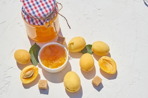 Hausgemachte bio-aprikosenmarmelade und reife aprikosen und brauner zucker auf weißem hintergrund.