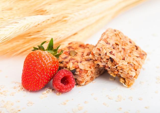 Hausgemachte bio-müsliriegel mit nüssen und getrockneten früchten auf weiß mit hafer und rohem weizen und erdbeeren