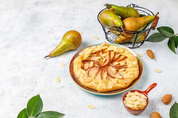 Hausgemachte birnen-galette-torte mit mandelblättern und frischen reifen grünen birnen