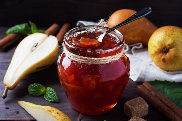 Hausgemachte birnenmarmelade in einem glas und frische birnen auf einem hölzernen hintergrund.