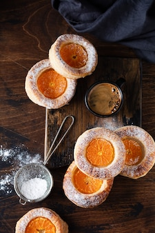 Hausgemachte blätterteig-mandarinen-brötchen ein alter weinlesekorb auf dunklem hintergrund. draufsicht.