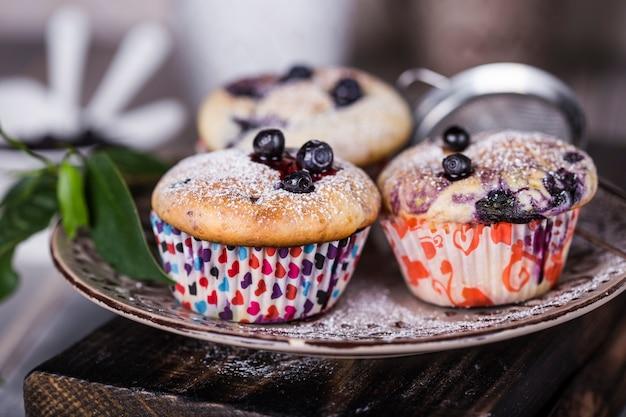 Hausgemachte blaubeermuffins mit puderzucker auf holzuntergrund