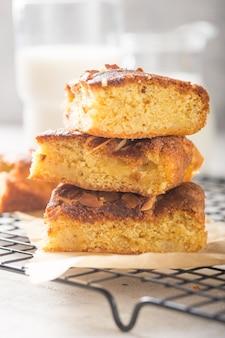 Hausgemachte blonde (blonde) brownies apfelkuchen quadratische scheiben mit glas milch