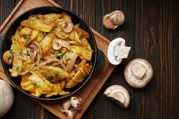 Hausgemachte bratkartoffeln mit zwiebeln, pilzen und knoblauch in einer pfanne auf einem holzbrett