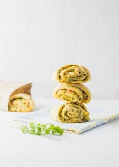 Hausgemachte brötchen mit knoblauch, grüner petersilie und paprika in einem serviettenweiß.