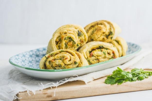 Hausgemachte brötchen mit knoblauch, grüner petersilie und paprika in einem teller mit serviette und holzschneidebrett weiß.