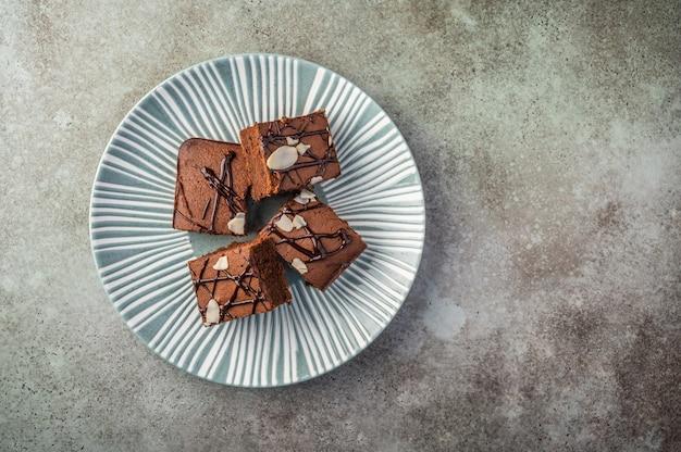 Hausgemachte brownies mit mandelblättern auf einem strukturierten teller auf einem hölzernen hintergrund.