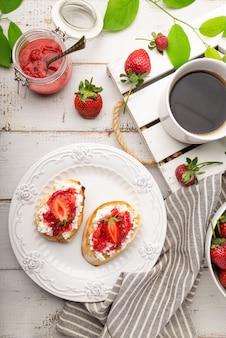 Hausgemachte bruschetta mit hüttenkäse und erdbeeren auf weißem holzhintergrund wooden