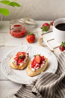 Hausgemachte bruschetta mit hüttenkäse und erdbeeren auf weißem holzhintergrund