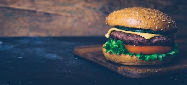 Hausgemachte burger (cheeseburger) mit rindfleisch auf einem hölzernen hintergrund. klassischer hausgemachter burger.