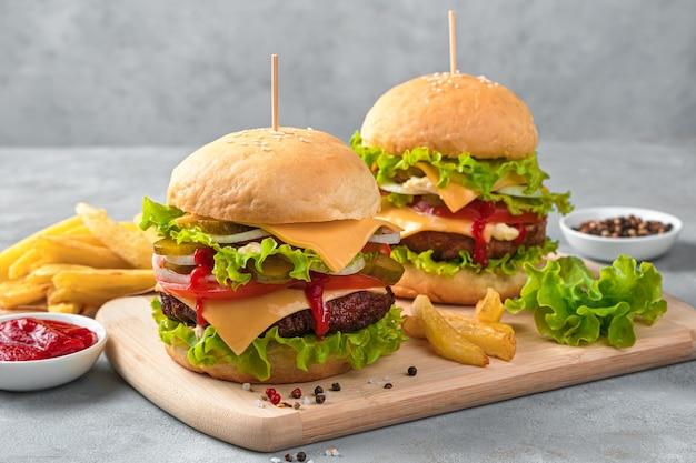 Hausgemachte burger mit rindfleisch, käse und gemüse an einer grauen wand. seitenansicht, horizontal.