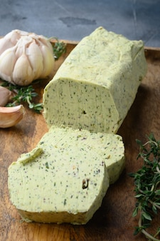 Hausgemachte butter mit thymian und rosmarin und zitronenschale auf grauem stein