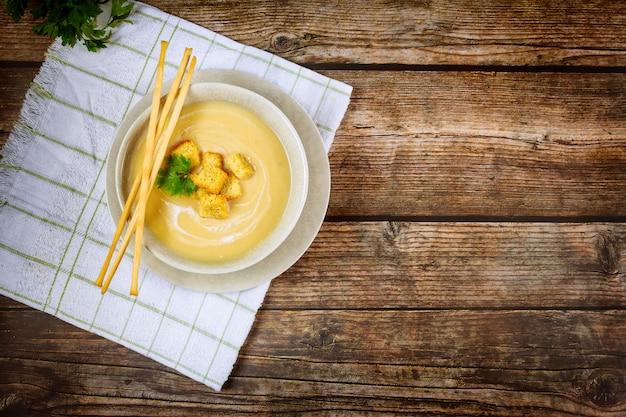 Hausgemachte cremige hühnersuppe in grauer schüssel, garniert mit knusprigen croutons.