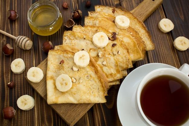 Hausgemachte crepes mit banane, nüssen und honig auf dem holzschneidebrett. blick von oben.