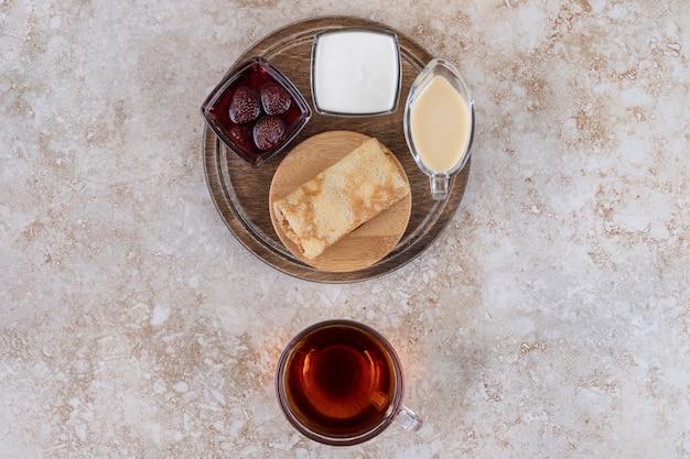 Hausgemachte crepes mit zuckerpulver und einer tasse tee