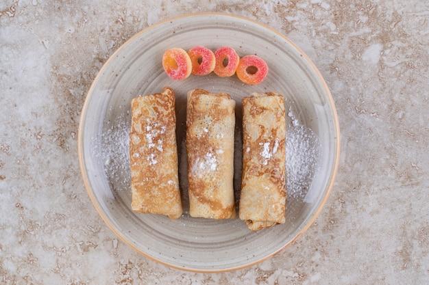 Hausgemachte crepes mit zuckerpulver und süßen marmeladen