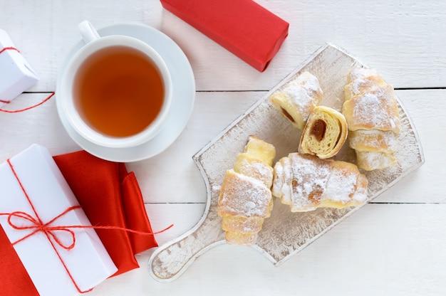 Hausgemachte croissants mit fruchtmarmelade, dekoriert mit puderzucker und einer tasse morgentee