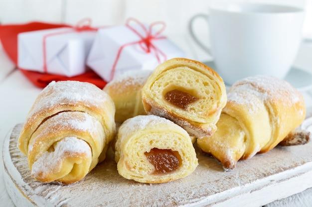 Hausgemachte croissants mit fruchtmarmelade, dekoriert mit puderzucker