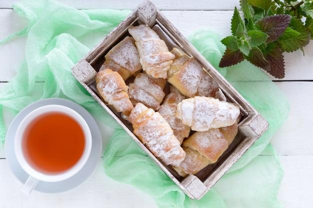 Hausgemachte croissants mit marmelade, dekoriert mit puderzucker und einer tasse morgentee