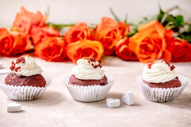 Hausgemachte cupcakes aus rotem samt mit schlagsahne in der reihe, weiße serviette mit band, rosenblumen, holzherzen über rosa beschaffenheitstabelle. valentinstag dessert.