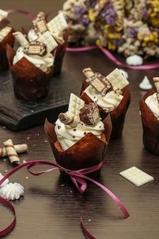 Hausgemachte cupcakes mit sahne auf einem dunklen hintergrund