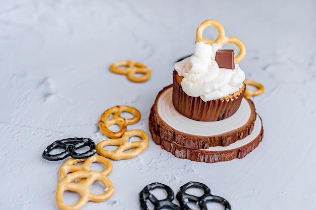 Hausgemachte cupcakes oder muffins mit schokolade, erdbeeren und brezeln