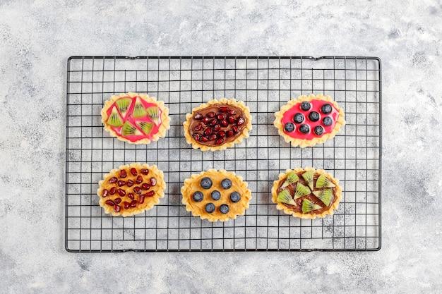 Hausgemachte desserts mit blaubeeren, kiwi-scheiben und granatapfelkernen.