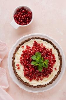 Hausgemachte dessertschokoladentarte mit kokoscreme und granatapfel und minze auf einem rosa tischhintergrund. draufsicht.