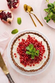 Hausgemachte dessertschokoladentarte mit kokoscreme und granatapfel und minze auf einer rosa tischoberfläche. draufsicht