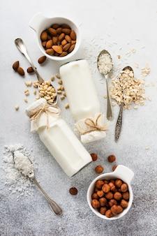 Hausgemachte diät gemüsemilch und mandeln, locken, haselnüsse, haferflocken, reis und kokosnuss auf einem grau. diät gesundes konzept.