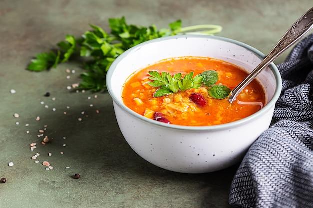 Hausgemachte dicke linsen-rote-bohnen-suppe mit gemüse garniert mit kräutern